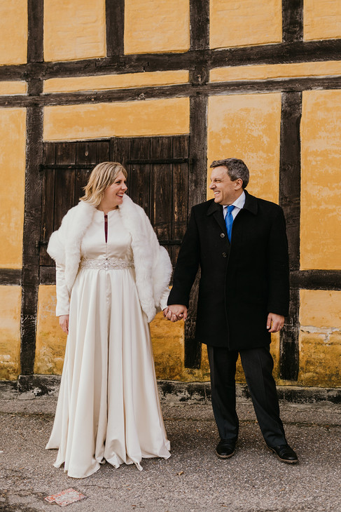 Newlyweds holding hands during their winter wedding adventure in Lolland Island after booking our Denmark elopement package