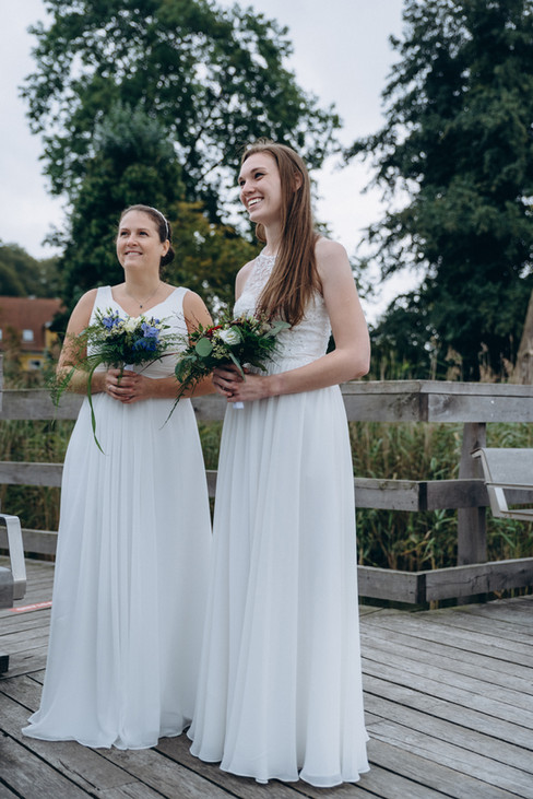 Two brides smiling and holding their bouquets as they enjoy their lesbian wedding in Denmark on Lolland Island.