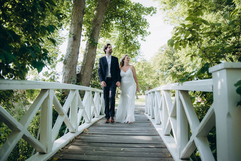 Husband and wife walking across a romantic wooden bridge during their adventure elopement in Denmark at the Lolland-Falster islands, one of the best places to elope for small weddings abroad.