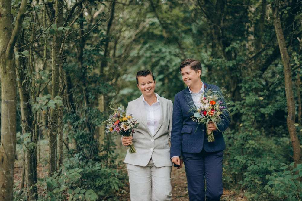 Lesbian couple walking in the forest as they get married in Denmark