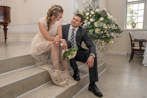 Newlyweds sitting at the stairs at the Bandholm Hotel as they wait for their marriage ceremony in Denmark