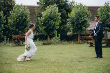 A bride running towards her husband, having an adventure after getting married in Denmark.