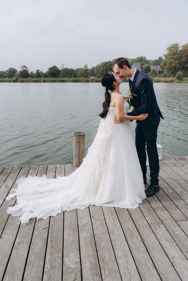 Newlyweds kissing by the Maribo Lake on Lolland Island during their Nordic Wedding in Denmark, one of our locations offered through our wedding packages abroad for two.