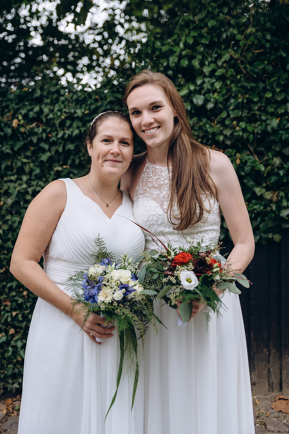 A lesbian couple posing to the photograph and each holding the beautiful summer bridal bouquet