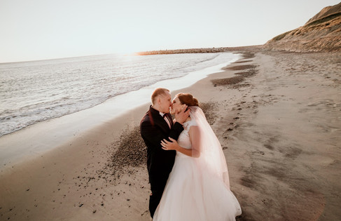 Newlywed kissing on the beach as they get married in Denmark