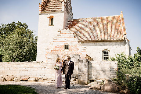 A couple standing in front of the ancient church, perfect for civil weddings abroad.