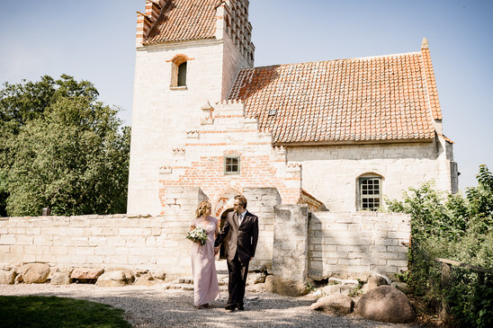 Newlyweds pictured in front of the history Old Hojerup church at Stevens Klint in Denmark, one of our top Denmark elopement packages for adventure weddings.