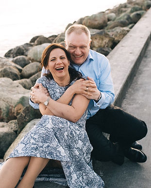 Victoria and Martin pictured laughing by the pier during their adventurous vow renewal abroad in Lokken, Denmark