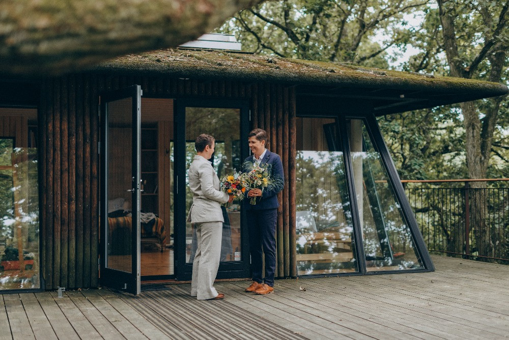 LGBT couple in the front of the tree hut in Denmark during their wedding