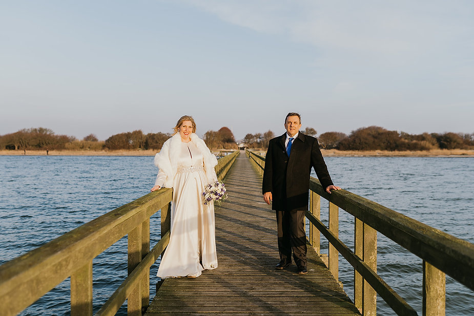 A couple at the Hestehoved Jetty during their Lolland island wedding in Denmark, one of the best places to elope for a winter wedding abroad.