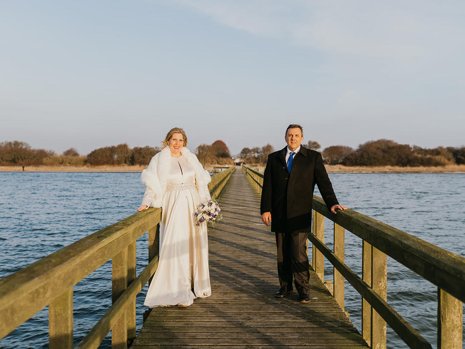 An American couple standing on the Hestehoved Jetty, one of the best destination wedding locations for couples looking for a laid back beach wedding abroad.