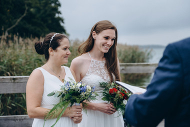 Two brides smiling during their lesbian wedding at the Maribo Lake in Lolland Island, one of the best places to elope abroad in Denmark.