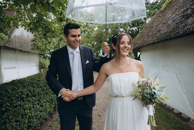 A groom holding an umbrella up for his bride during their intimate wedding abroad in Denmark