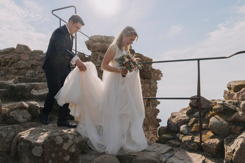 A groom holding his wife's wedding gown as they walk through the Hammershus Ruins on Bornholm Island, a great Denmark wedding venue for intimate weddings abroad.