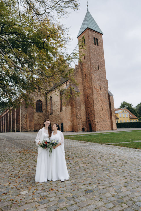 A lesbian couple in front of the Great Cathedral in Maribo on Lolland Island during their same-sex wedding in Denmark.