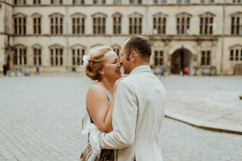 An intimate moment between husband and wife as they embrace each other and smile during their adventure wedding in Hamlet's Elsinore Castle in Denmark