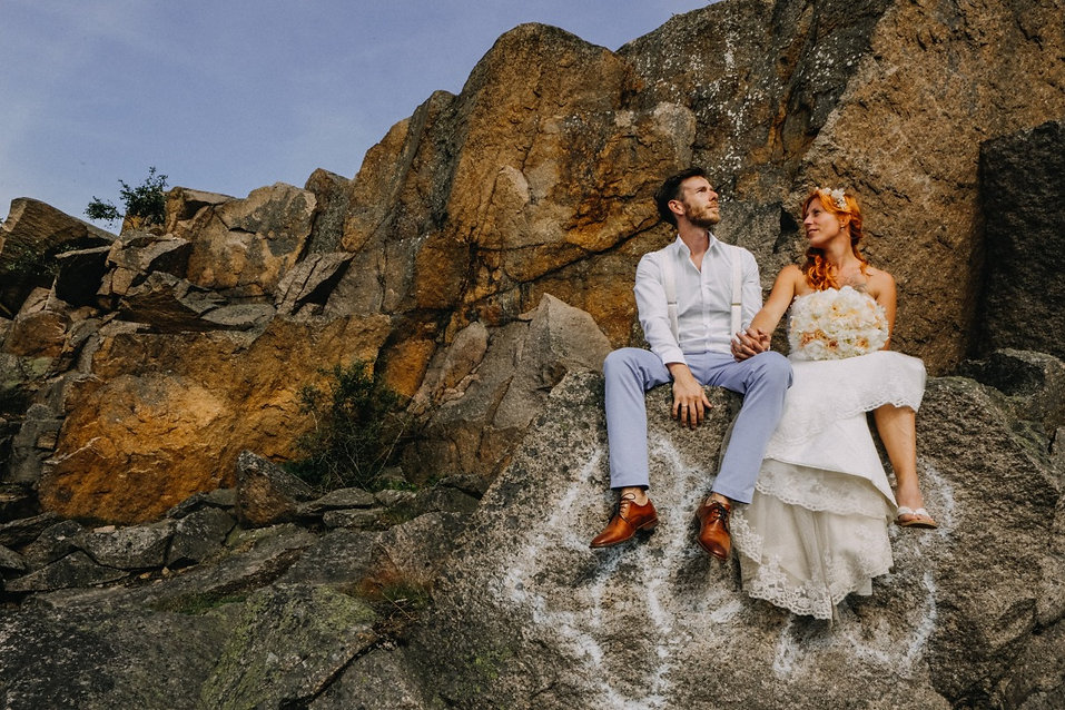 A couple embracing romantically, sitting on the cliffs during their outdoors wedding in Denmark's Hestehoved Jetty made possible by our adventure elopement packages.