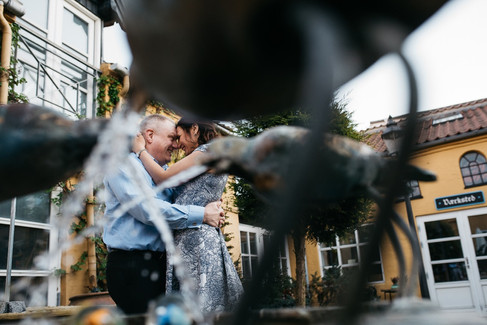 Man and wife hugging and gazing happily into each others eyes during while they renew their vows abroad.