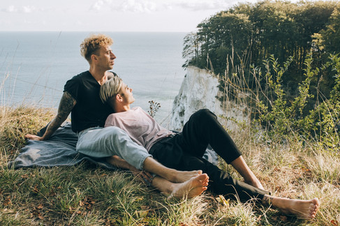 Newlyweds sitting at the top of Mons Klint enjoying the view as they get married in Denmark, the destination they chose for their dream LGBT wedding