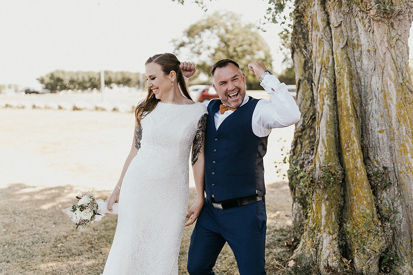 A bride smiling as her groom pumps his hands up in excitement during their Nordic wedding in Denmark