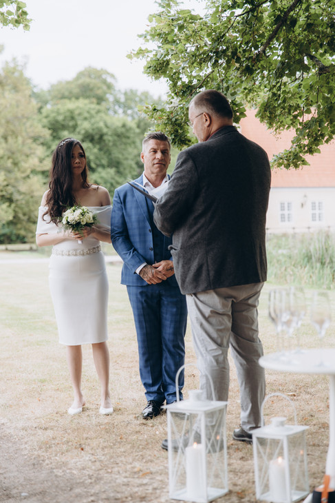 A stylish couple hearing their oats while getting married in Denmark in a romantic location outside of a castle, one of our best Denmark elopement packages.