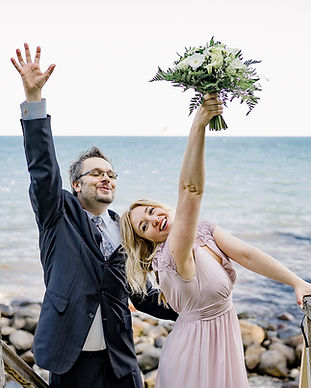 Newlyweds lifting up their hands in celebration of their adventure elopement to Denmark, pictured at Stevens Klint, one of the most romantic wedding venues.