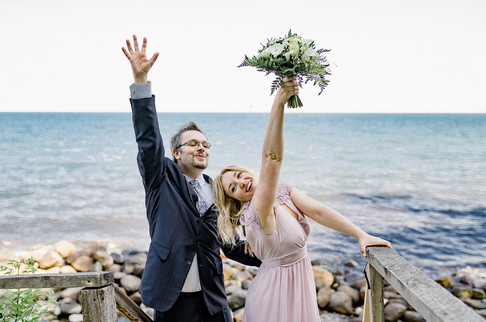 Newlyweds raising their hands up in the air in happiness during their adventure wedding abroad in Denmark.