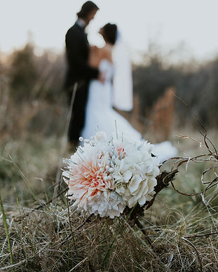 A picture of a flower with newlyweds in the background during their romantic adventure elopement to Denmark.