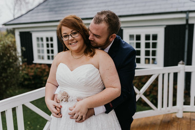 A groom hugging his smiling bride from behind as they enjoy their wedding in Denmark