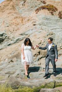 a couple walking between rocks on bornholm