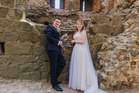 A bride and groom posing inside the Hammershus Ruins during their adventure elopement in Denmark at Bornholm Island.