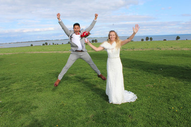 A groom jumping for joy and his wife radiating as they enjoy their Scandinavian wedding on the twin islands of Lolland-Falster in Denmark.