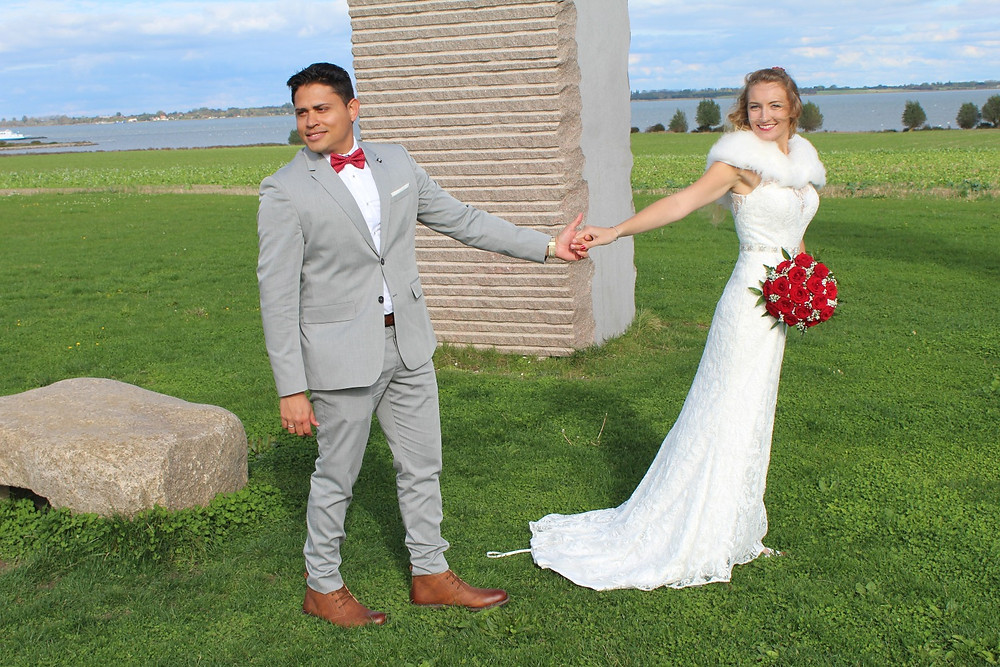 Newlyweds holding hands at the Dodekalitten - a great wedding venue in Denmark