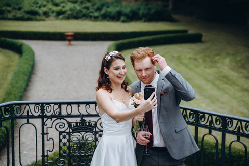 Newlyweds taking a selfie during their castle wedding in Denmark, pictured at Vindeholme Castle, one of the best places to elope for an intimate wedding abroad.
