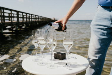 Pouring champagne by the Hestehoved Jetty on Lolland Island, one of the many details we take care of in our Denmark elopement packages