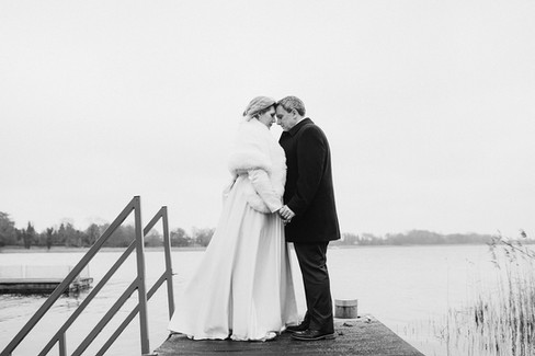 Newlyweds embracing and holding hands by the water during their winter wedding adventure in Denmark.