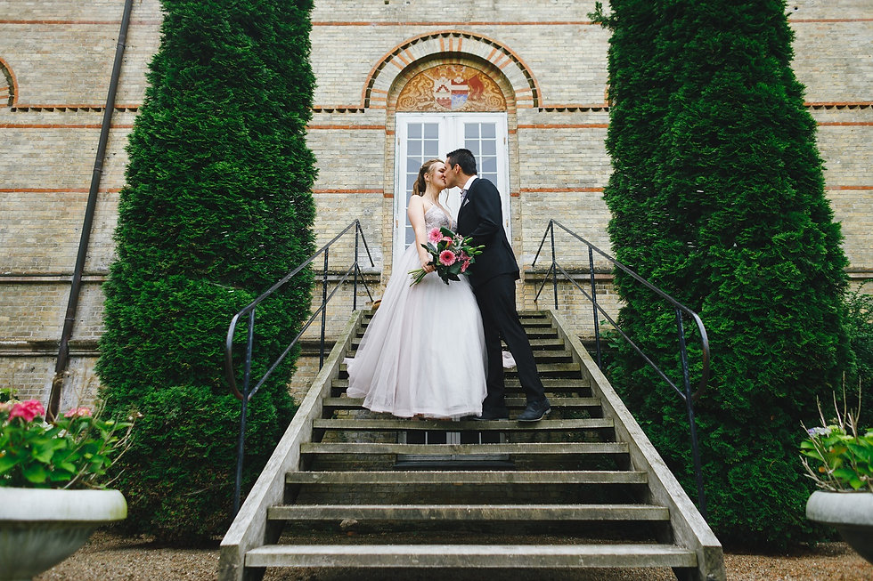 A couple kissing in front of a Denmark castle during their adventure wedding on Lolland Island, one of the best places to get married abroad.