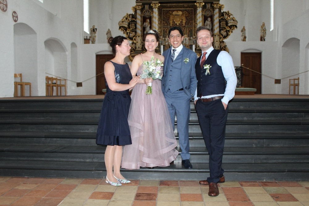 Newlyweds with friends in Maribo cathedral after they got married in Denmark