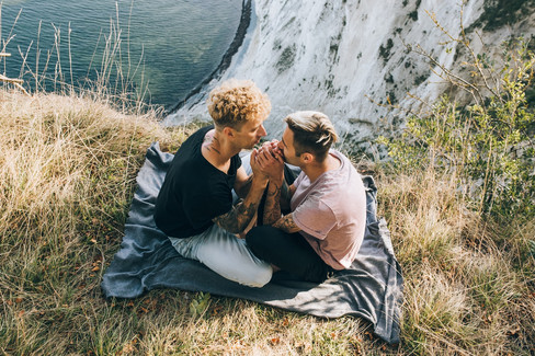 A gay couple sitting at the top of Mons Klint as they celebrate their same-sex wedding in Denmark