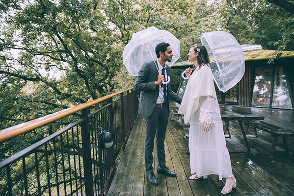 A groom and bride laughing and having fun in the rain during their small destination wedding in Denmark.