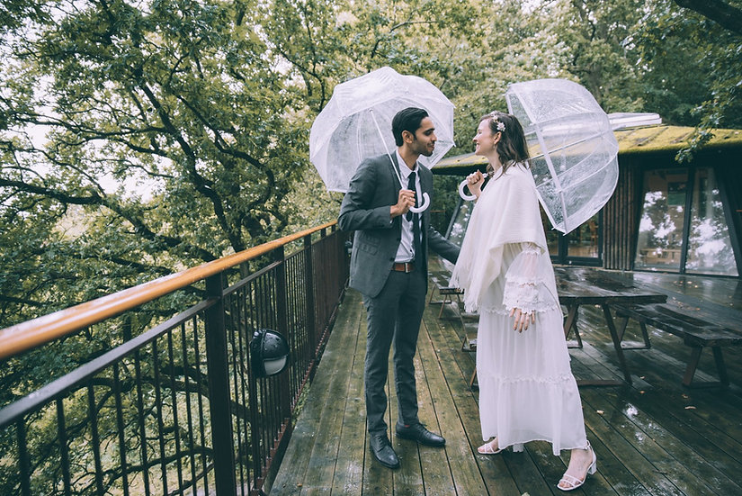 A couple celebrating their elopement abroad during the rain on top of a Nordic treehouse because they booked an elopement wedding package from Nordic Adventure Weddings.