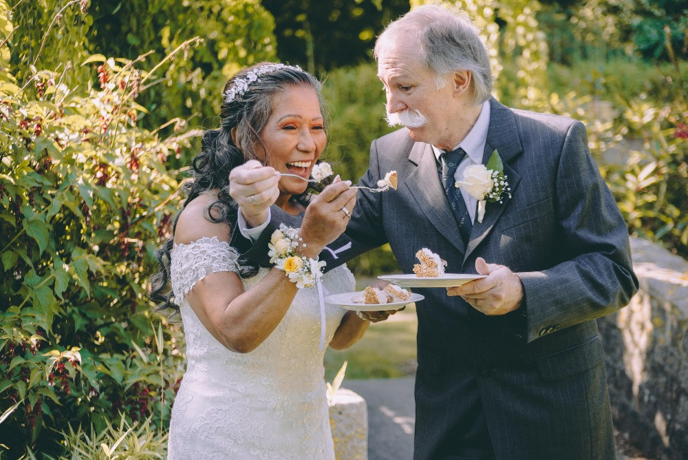 Aged couple have fun eating their wedding cake at their Danish wedding
