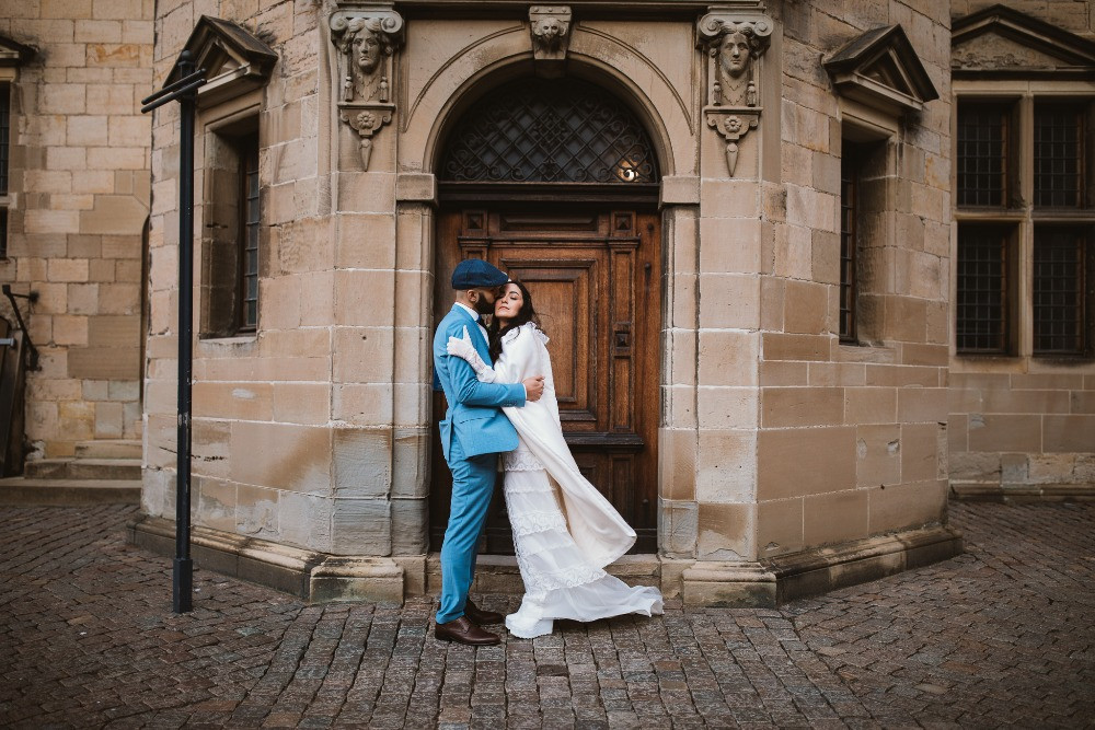 A groom kissing his bride in the front of Kronborg castle where they got married