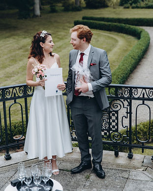 Newlyweds looking at each other with their wedding certificate at the Vindeholme Castle during their Denmark elopement abroad, a great marry abroad idea
