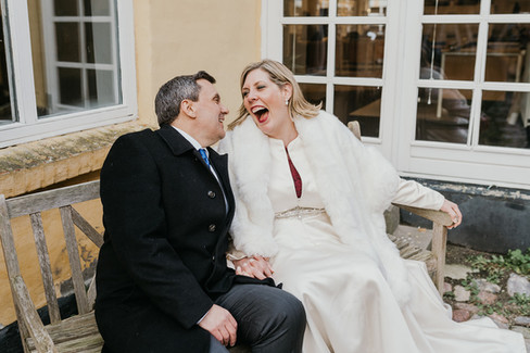 Newlyweds sitting on a bench and laughing during their intimate wedding abroad in Denmark