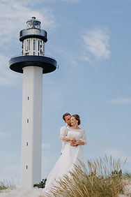 A groom hugs his bride near the lighthouse on the wedding island Bornholm, where couples elope just 2 of them
