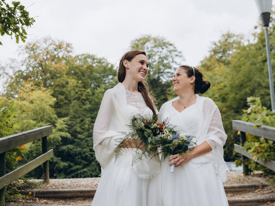 two brides holding their bouquets and smiling at each other during their lesbian wedding in Denmark, a country where same-sex marriage is legal.