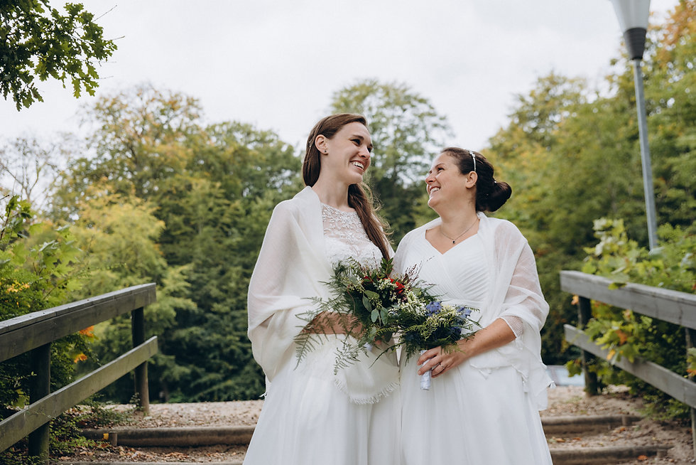 Two brides holding bouquets during their gay marriage in Denmark, enjoying their same-sex wedding abroad