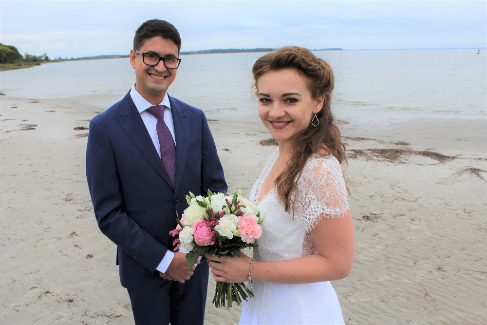 A couple just have their Danish wedding on the beach and the bride holds the wedding bouquet with colorful roses
