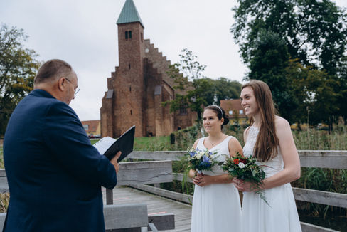 A gay couple enjoying their LGBT wedding ceremony at Lolland Island by the Maribo Lake, one of the best places to get married abroad in Denmark.